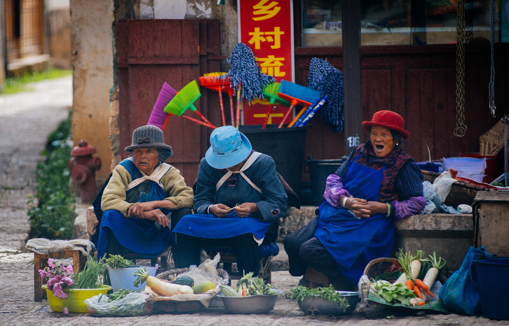 Naxi women sell produce in the village main square.