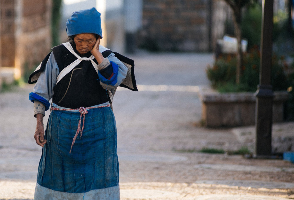 Naxi woman walks to work with an empty basket on her back.