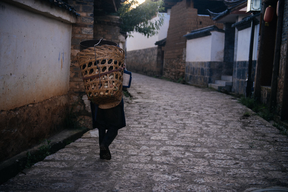 A bit before sunset, a Naxi woman returns home with a basket full of corn.