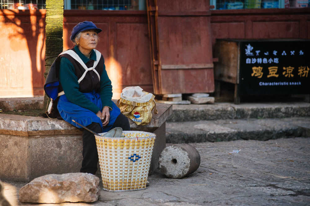 Woman waits for customers to sell fruit from her basket.