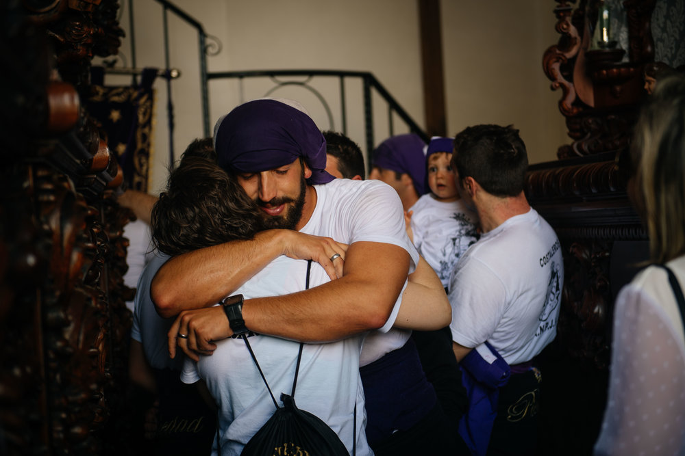 Antonio Caparrós hugs a relative with tears in his eyes as he walks out from under the statue he was carrying. Caparrós every year takes part in the procession in memory of his late uncle that did it before him.