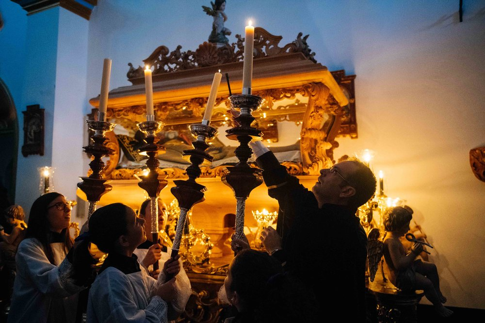 Altar children have their candles lit before Holy Friday's procession. In the back, a coffin with an image of the body of Christ.