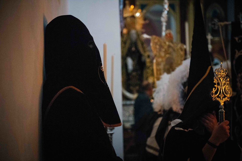 Costalero leans against the wall moments before lifting a 1.1 ton statue of Christ. They wear black clothing and hoods to seem invisible at night and the imagem of Christ appear floating on the streets.