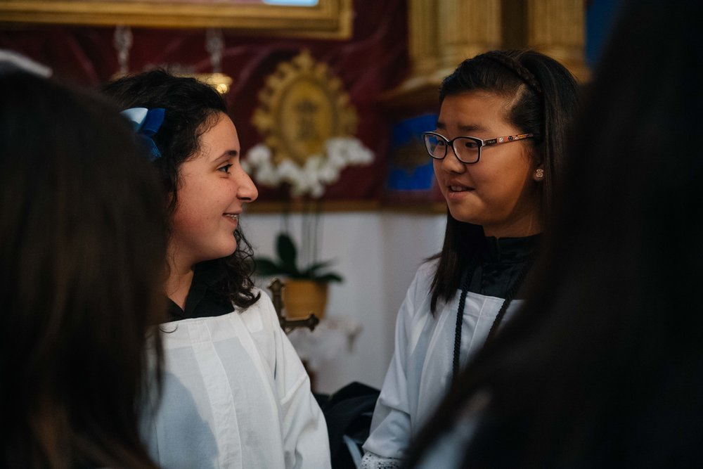 Maria José Rodriguez talks to another altar girl inside the church before the start of the procession.