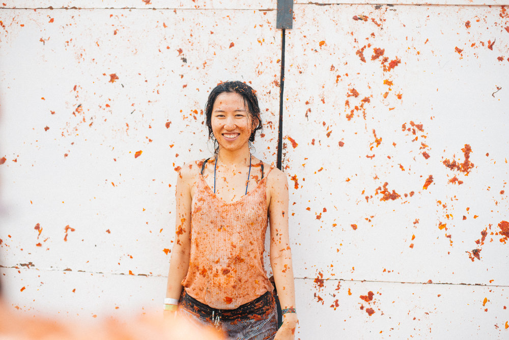 Chinese soldier celebrates surviving the Tomatina. Her shirt is white. Or at least it was.