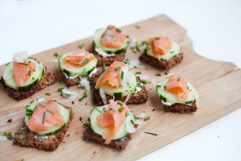 Toast served with St. Môret cheese spread, a slice of cucumber, smoked salmon, chives, and white onions.
