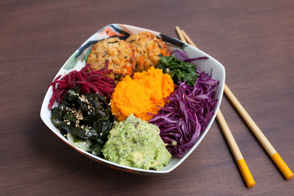 Brown rice and quinoa mix topped with hijiki tofu patties, beetroot, cucumber wakame sunomono, red cabbage, spinach, crushed avocado with yuzu and poppy seeds, and carrot ginger dressing.