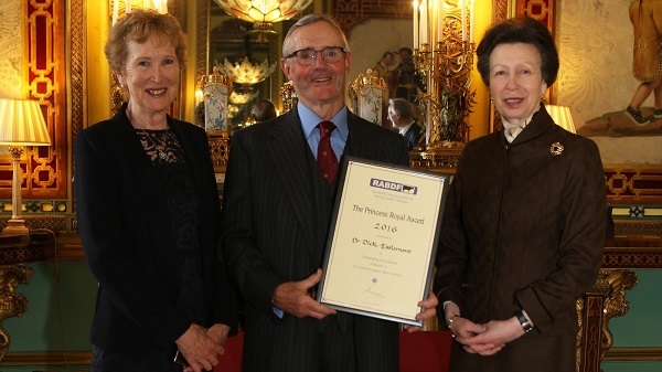 Dr Dick Esslemont (centre) with wife Bridget (left) receiving his presentation from Her Royal Highness