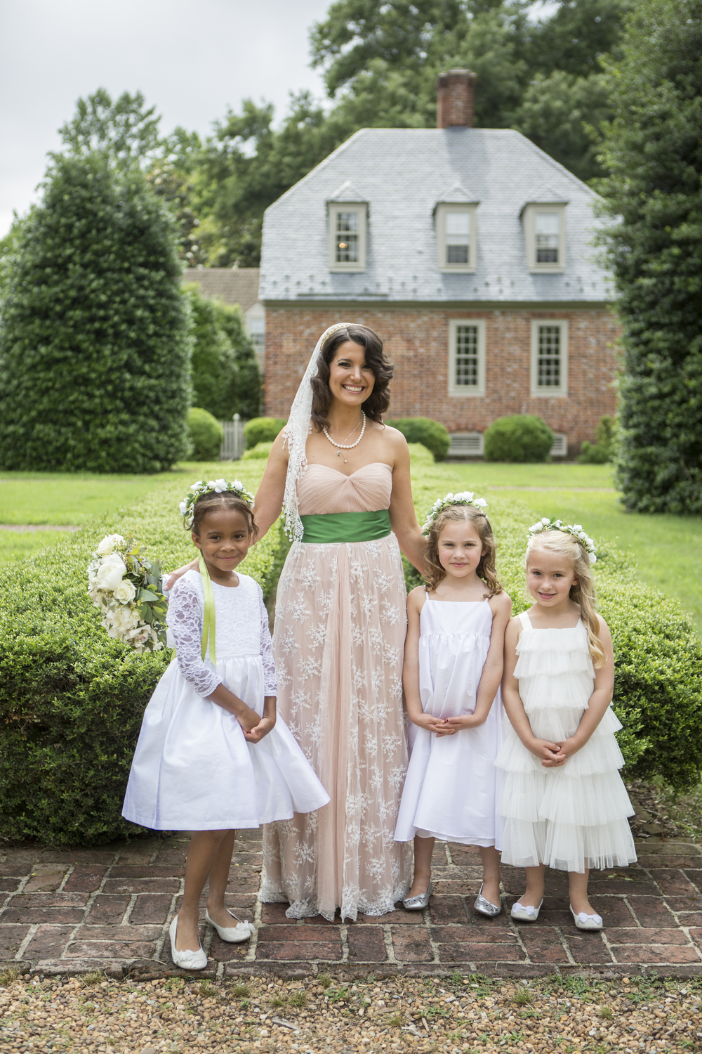 Flower girls pose with the bride in front of the Manor