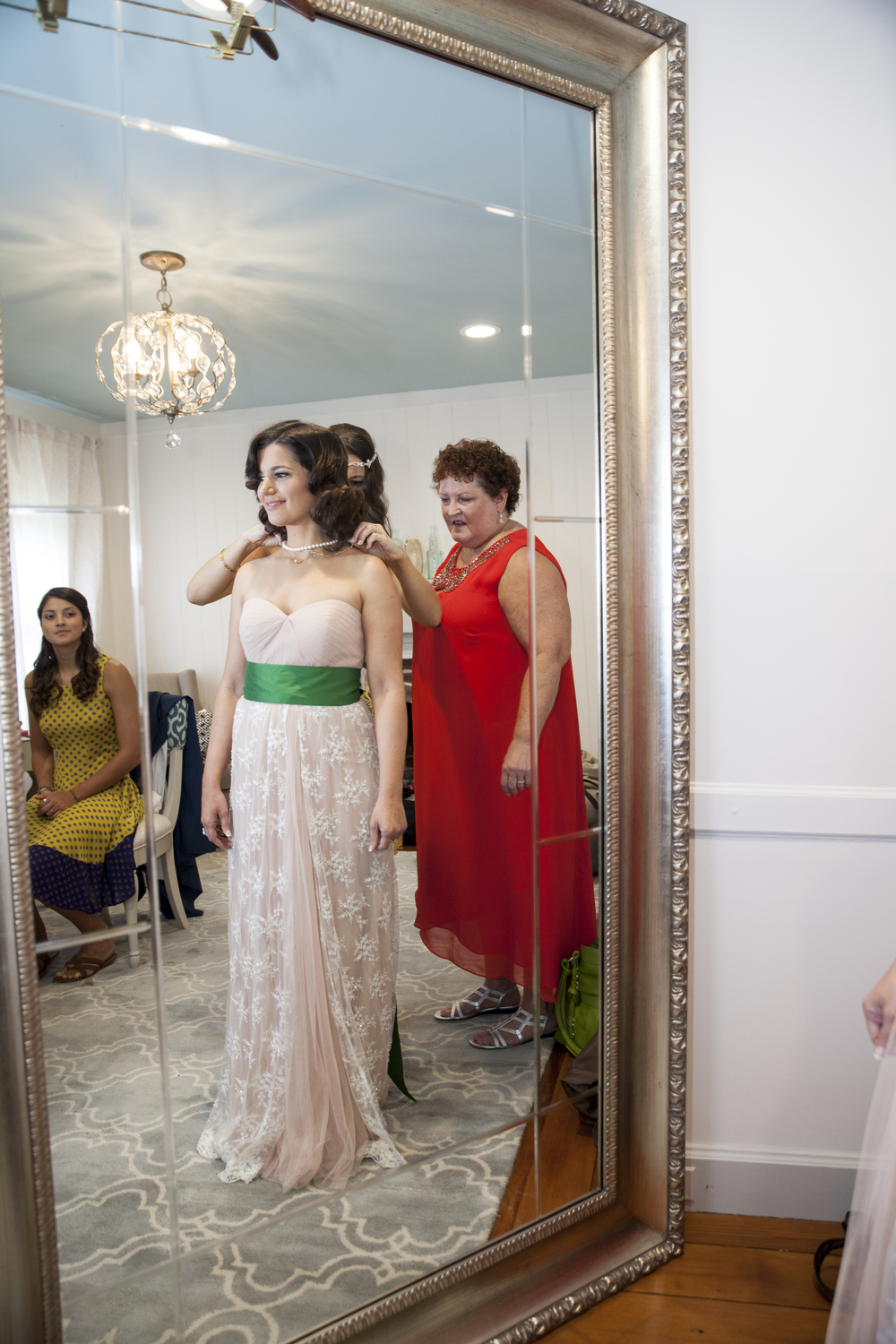 Wedding attendants help the bride prep for the ceremony