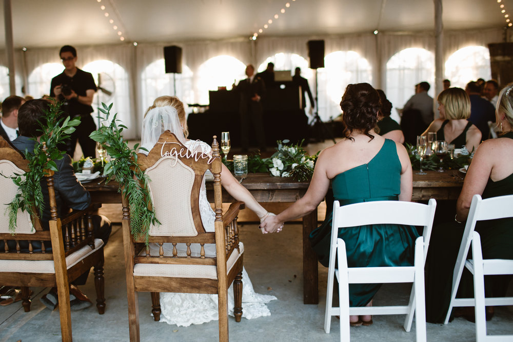 bride and maid of honor holding hands as sisters