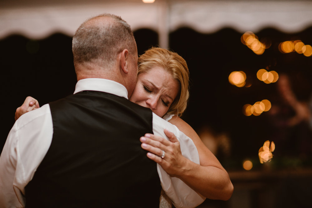 bride crying while dancing with her dad