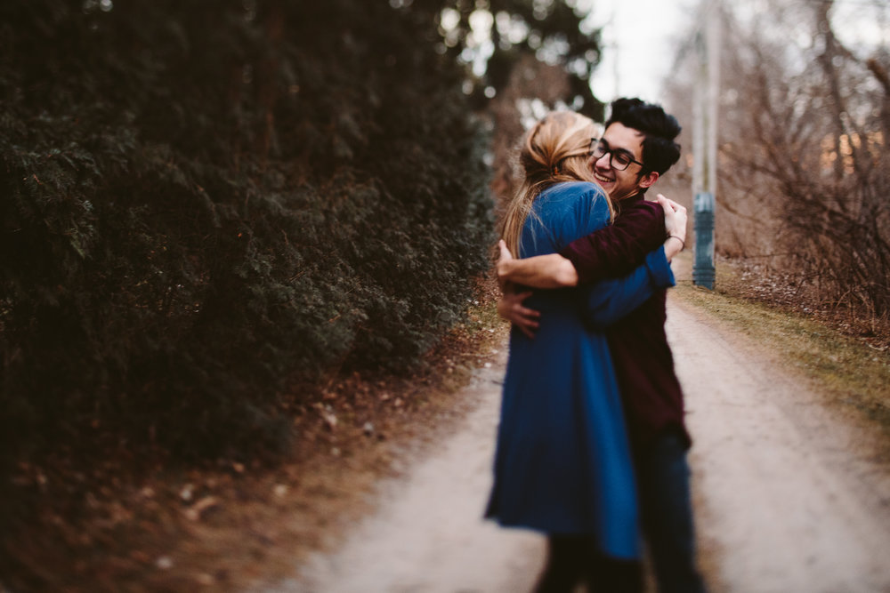 couple embracing during traverse city forest engagement