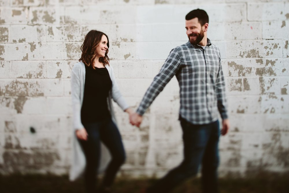 couple walking and holding hands traverse city engagement