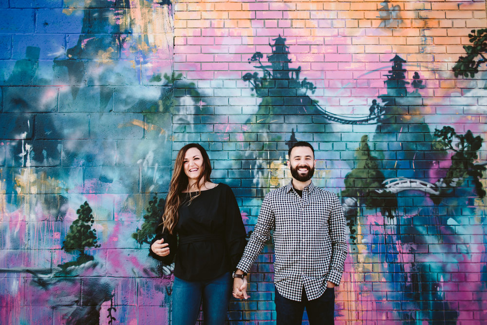 eastern market couple in front of murals
