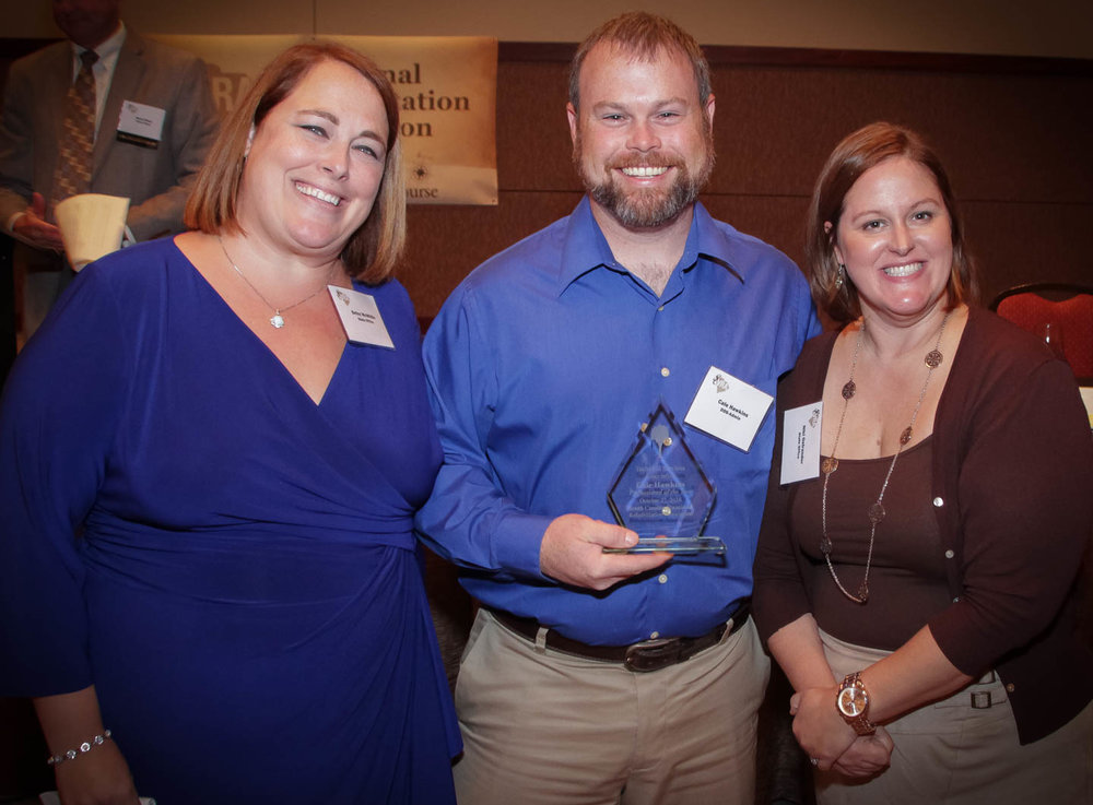 Cale Hawkings (center), Information Resource Specialist, accepts the Technical Services Association Award from Betsy McWhite (left) and Niki Ostrander.