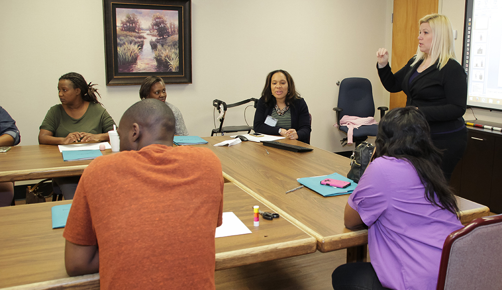 Shonna Magee, Deaf and Hard of Hearing Coordinator (standing), and Kayla Wright, Occupational Therapist (center, seated), lead a class for Deaf clients at the Evaluation Center.