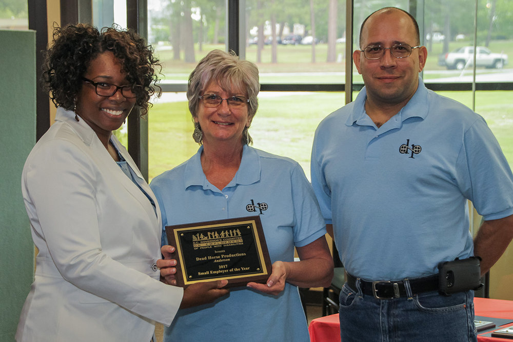 Berdina Hill (left), counselor with the SC Vocational Rehabilitation Department and representative of the Anderson Mayor's Committee on Employment of People with Disabilities, presents the Small Employer Award to Linda Lavold and Vic Aviles of Dead Horse Productions.