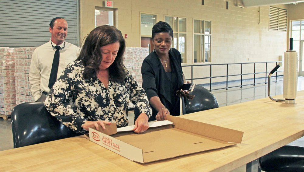 As Ryan Skinner, Upstate Regional Business Development Specialist and Felicia Johnson, Interim Commissioner observe, Dr. Roxzanne Breland, Agency Board Chair, demonstrates package assembly at VR's new Training Center located at the Bryant Center in Lyman.