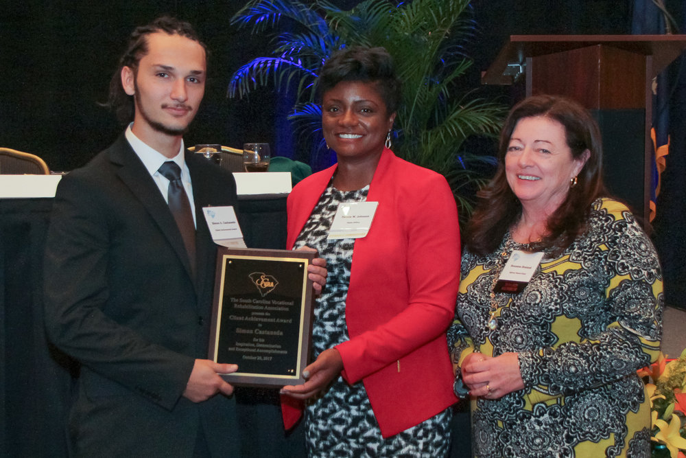 Simon Castaneda (left) receives the 2017 Client Achievement Award from Felicia Johnson, VR Interim Commissioner, and Dr. Roxzanne Breland (right), Chair of the SC State Agency of Vocational Rehabilitation.