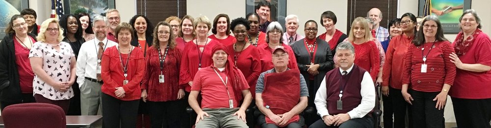 Disability Determination Services staff in Columbia wear red for women's heart awareness. Three of the individuals pictured are heart disease survivors, each of whom had open heart surgery.