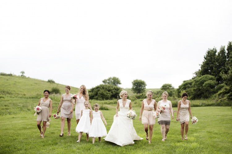Wedding bridal party walking in grass field