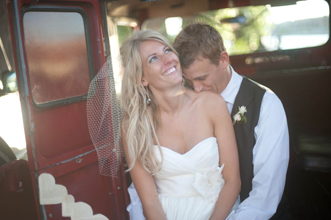 Groom Kissing Bride on the shoulder in old truck