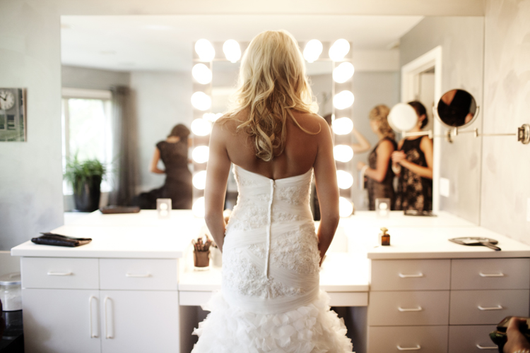 bride looking at herself in wedding dress in a mirror