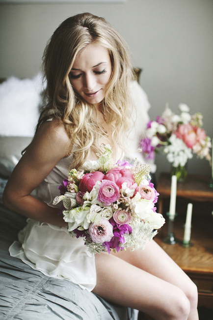 Bride with floral bouquet on bed