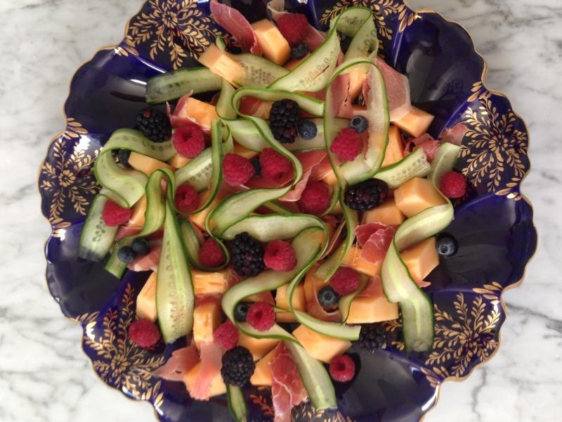 Antepasto de presunto cru com melão orange, fitas de pepino e frutas vermelhas.
