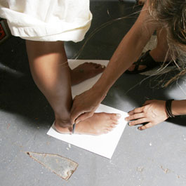 Have somebody trace your feet by standing with each foot on a separate piece of paper.  The paper should be big enough to have space around each foot when you stand on it.