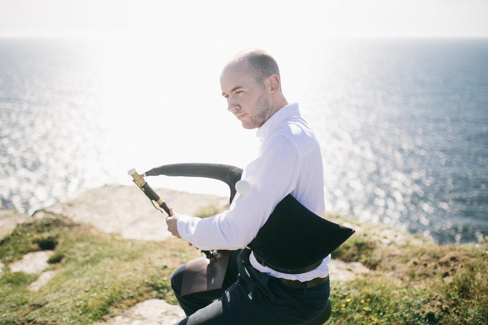 Uilleann piper playing Irish music at cliffs of mother.jpg