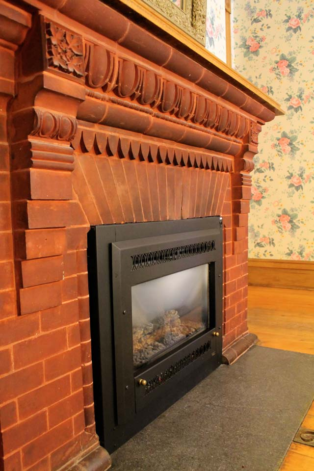 Gas Fireplace of Conservatory- Room 1 featuring antique brick with egg and Dart pattern.