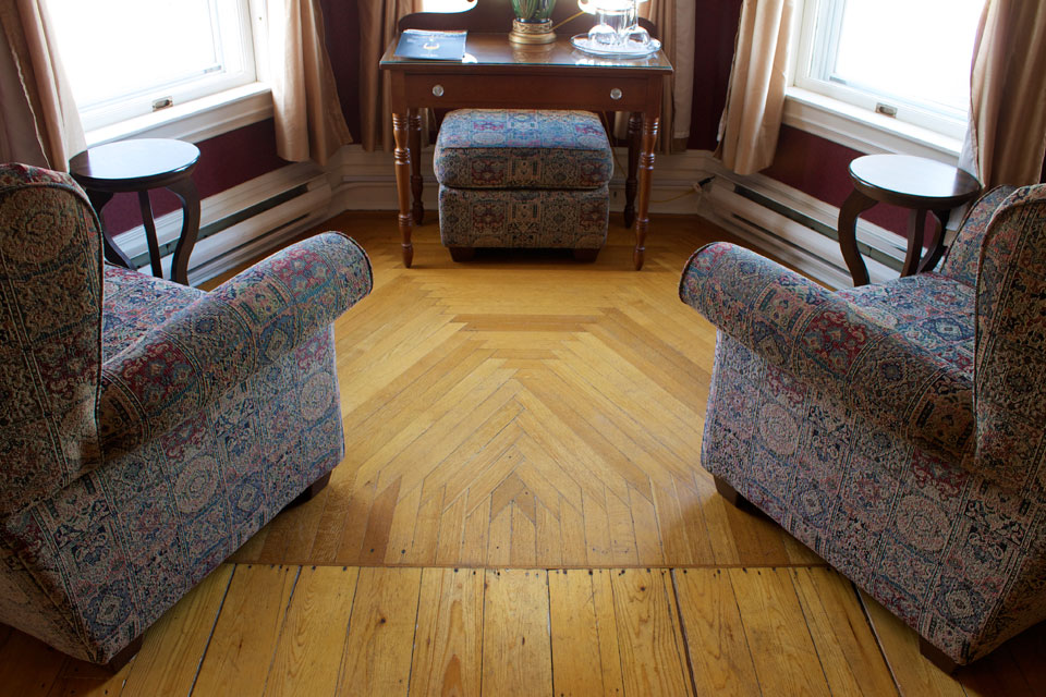 Pair of wingback armchairs in bay window with Antique oak floor of Room 4 at the Willard Street inn.