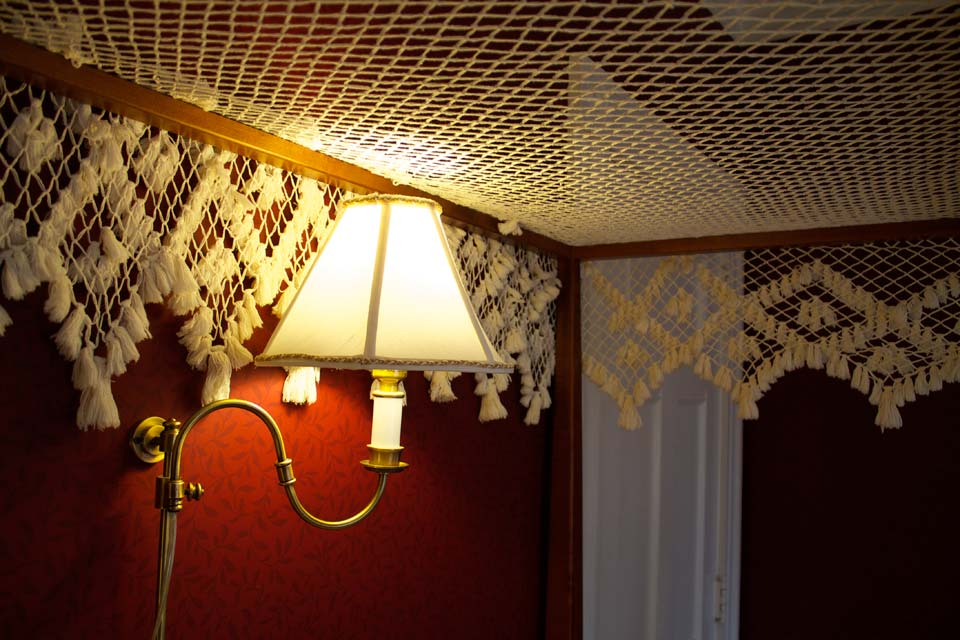 Wall mounted brass sconce over bed illuminating stitched decorations of canopy in Champlain Lookout Room.