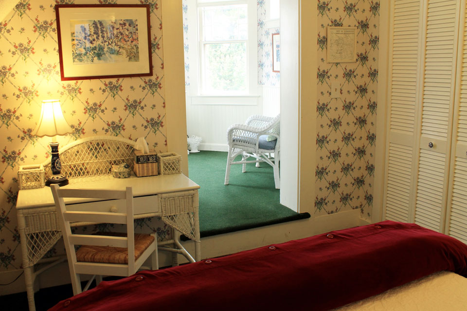 Sunny tower room with sitting area and writing desk at the Willard Street Inn, offering fantastic breakfasts and historic charm