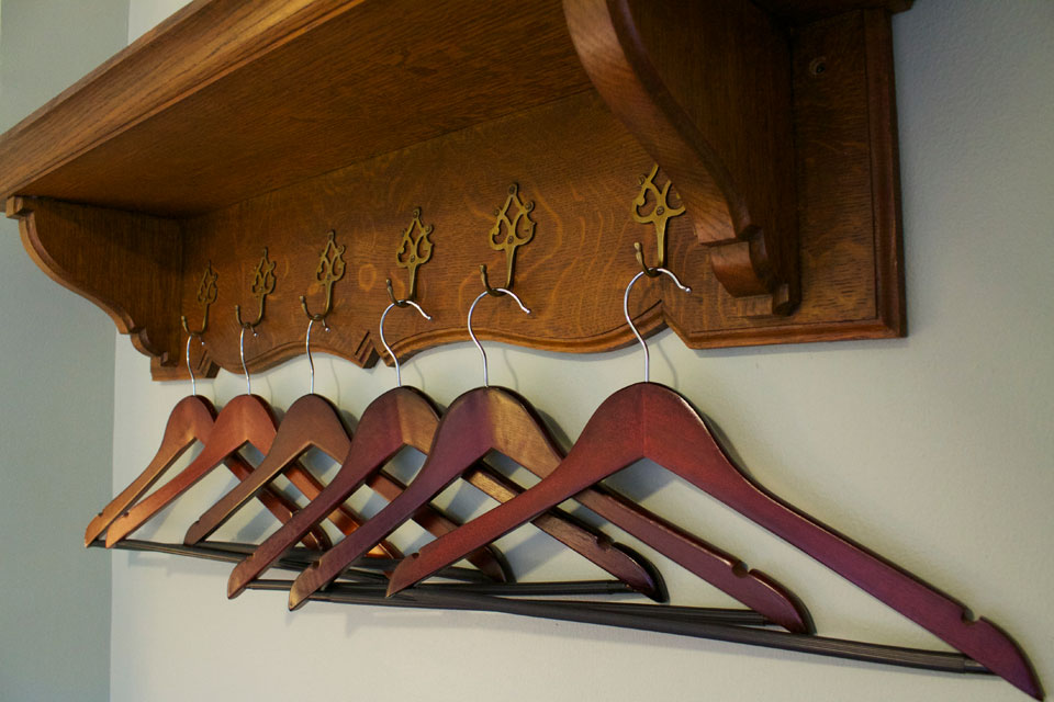 oak wall shelf with plenty of hangers for your traveling cloths in Room 15.