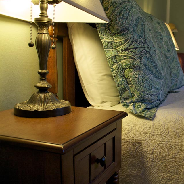 Wooden bedside table provides a perfect place for a good book next to Lindsey's Loft double bed with wooden headboard.