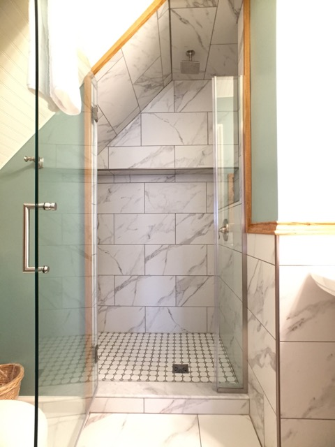 Tiled shower with bench makes wonderful use of space in the bathroom of Room 11.