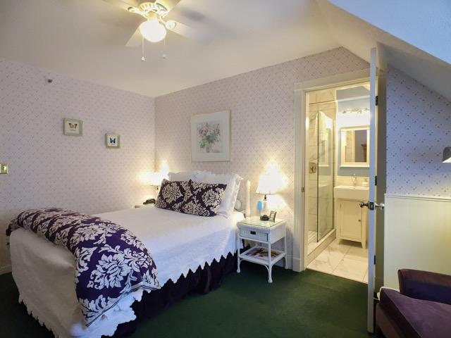 Queen bed with plush bedding of Periwinkle room in Burlington's Willard Inn.