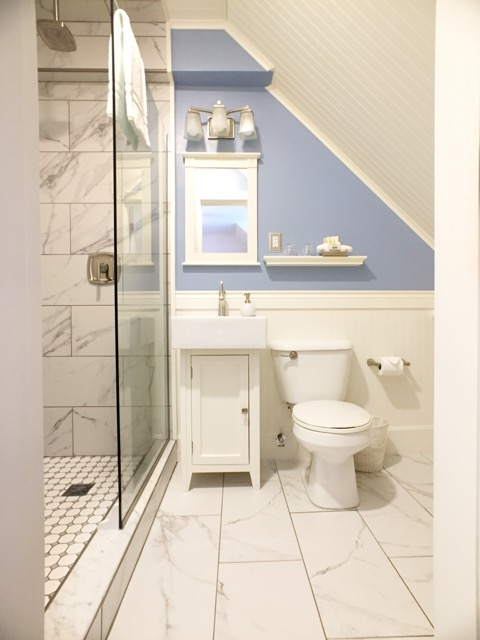 Bath of Room 9. THe large, tiled walk-in shower and rainfall shower head complete the luxurious accommodations.