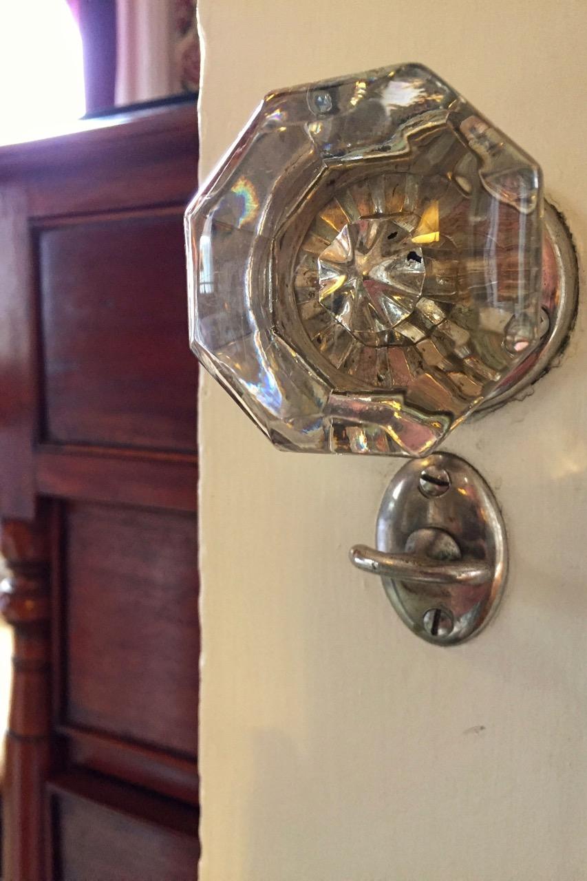 Close-up of antique glass doorknob of bathroom door in Victorian Cabernet at WSInn.