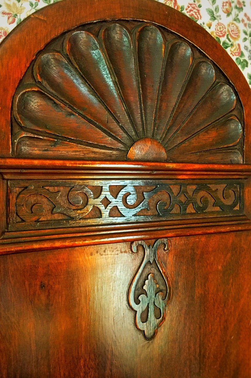 Details of wooden carvings atop of the antique armoire in Room 2.