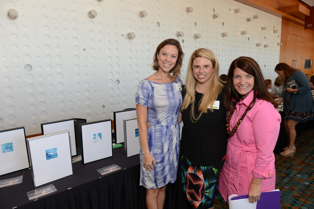 Local artist Molly Howell with board members Whitney Akin and Callen Martin. The framed artwork on the table is from a tree collage painting made by ESTN survivors.