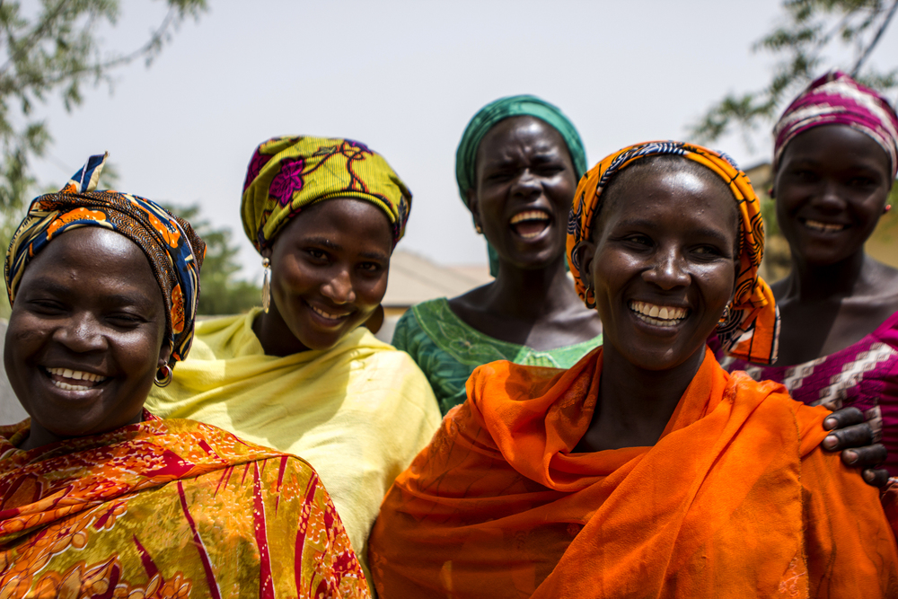 Yola, Nigeria. March 1 2015. A group of women joke with one another after a food distribution at a local church. Many of the internally displaced people (IDPs) are living with friends and family from their hometown, ev  en though they have settled in a new city