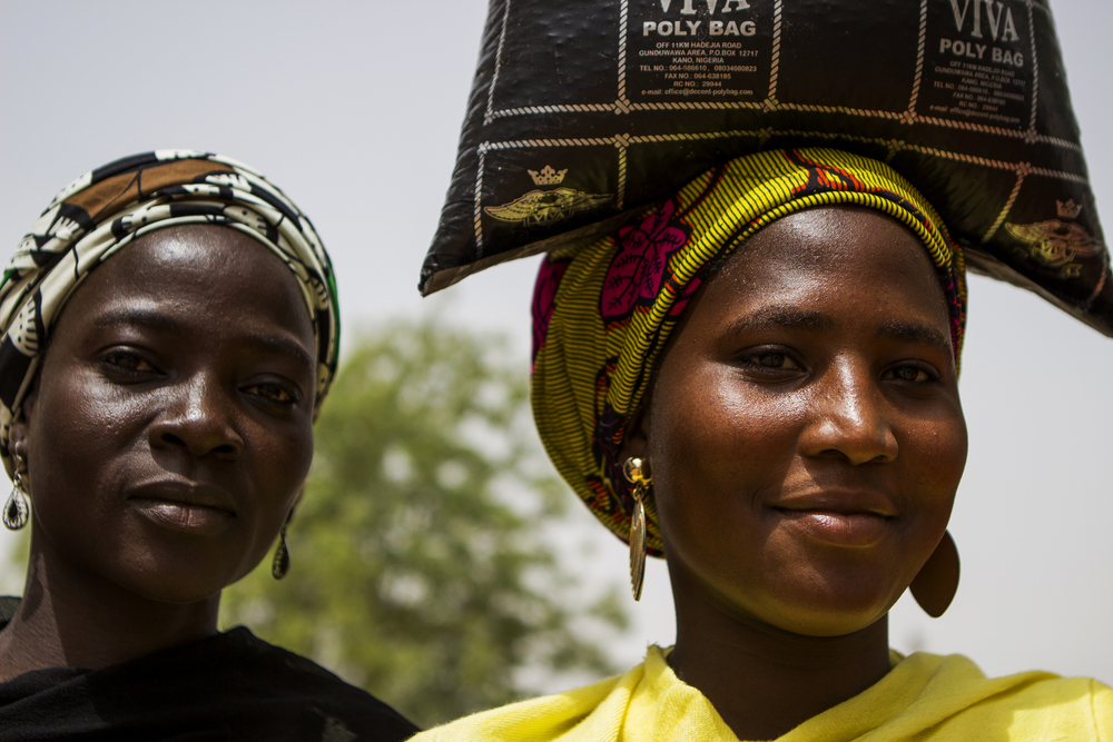 Yola, Nigeria, March 3, 2015. Women carry bags of donated food after a distribution at a local church. Though aid groups have been providing massive amounts of supplies, there is never enough for everyone.