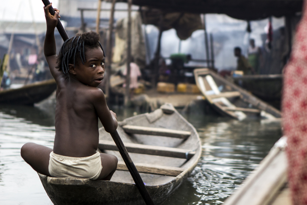 Lagos, Nigeria. Feb. 26, 2015. A boy poses for a photo while steering his canoe in the floating village of Makoko. Here, children start to steer their own boats at 7 years old.