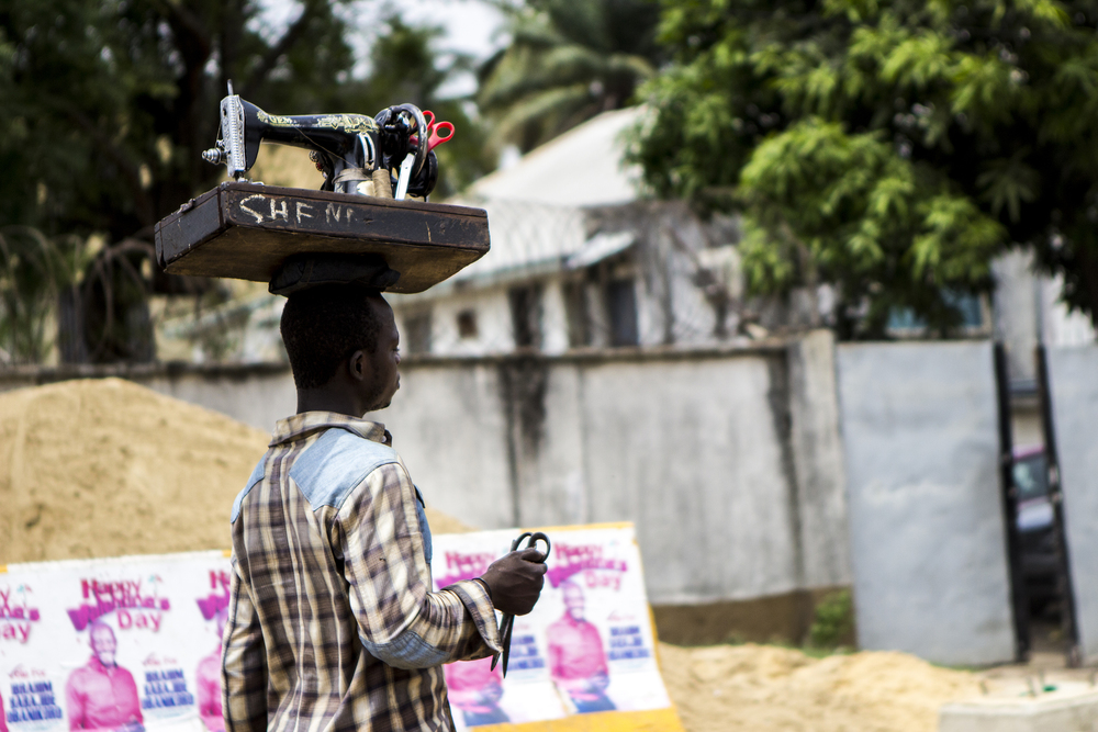 A man balances a sewing machine on his head as he offers services by the side of a highway in Lagos, Nigeria on Feb. 25, 2015.