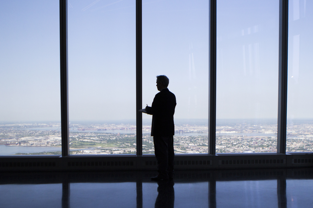 A reporter stands near a viewing window at the One World Trade Center Observatory in New York City on May 29, 2015.    Shot for the Village Voice.