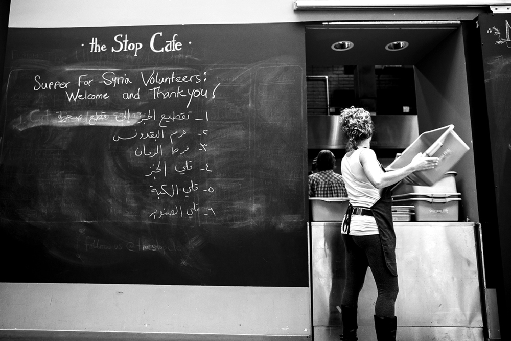 """A volunteer helps clear dishes at The Stop Cafe inside Toronto, Ontario. She's one of dozens of volunteers who helped prepare meals for 500 people at """"Supper With Syria"""" on November 29, 2015. The event's goal was to raise the $70,000 necessary to legally sponsor and support two Syrian refugee families to be resettled in Toronto's Ward 21. 